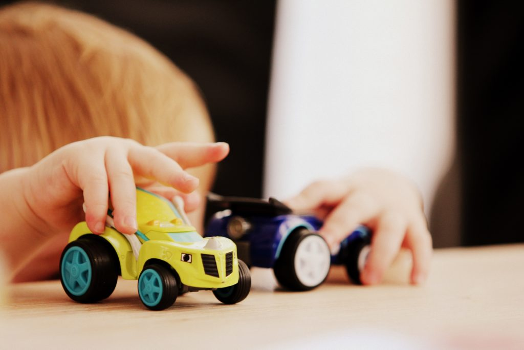 A boy plays with his cars from his toy rotation.