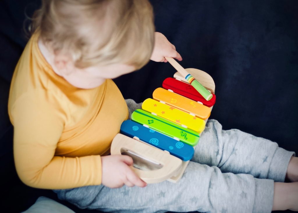 A boy plays with a musical toy from his toy rotation.